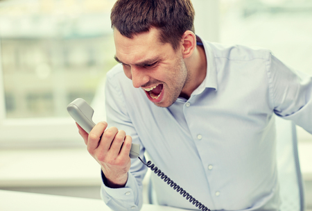 yell: business, people, emotions, stress and communication concept - furious businessman calling on phone in office