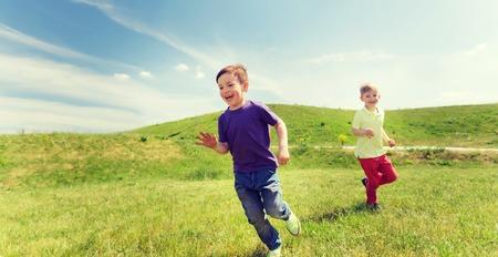夏には、幼年期、レジャーおよび人々 のコンセプト - 幸せな男の子と緑のフィールドに屋外を実行するタグ ゲームをプレイ
