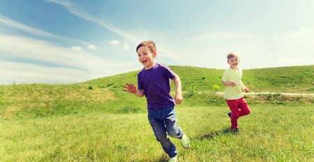 catch: summer, childhood, leisure and people concept - happy little boys playing tag game and running outdoors on green field