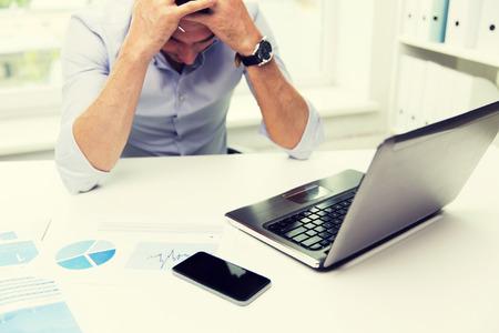 tecnología informatica: negocio, la gente, fall, el papeleo y la tecnología concepto - hombre de negocios con ordenador portátil y documentos de trabajo en la oficina
