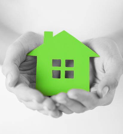 Immobilien und Familie zu Hause Konzept - Großansicht Bild der weibliche Hände, die grüne unbelegte Papierhaus