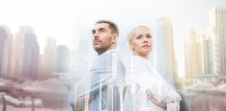 copyspace: business, partnership, success and people concept - businessman and businesswoman standing over dubai city background with double exposure effect