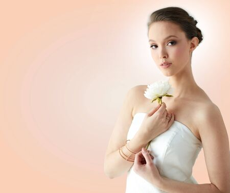 beige: beauty, jewelry, people and luxury concept - beautiful asian woman or bride in white dress with peony flower, golden ring and bracelet over beige background