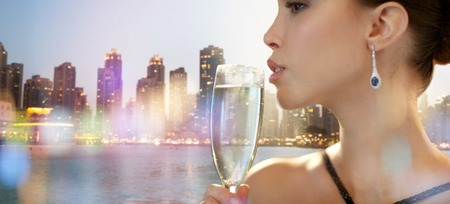 party night: holidays, nightlife, drinks, people and luxury concept - close up of beautiful young asian woman drinking champagne at party over dubai city night lights background Stock Photo