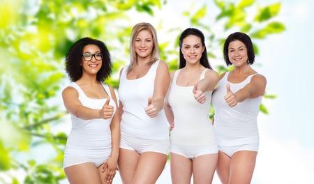 제스처, 우정, 아름다움, 우리 모두의 몸 긍정적이 고 사람들이 개념 - 녹색 자연 배경 위로 엄지 손가락을 보여주는 흰색 속옷에 행복 한 다른 여자의  스톡 콘텐츠