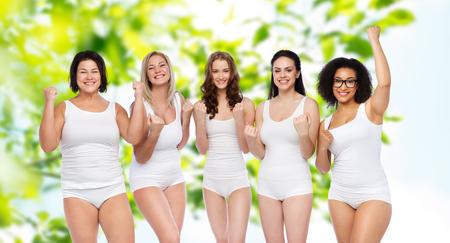 éxito, amistad, belleza, cuerpo positivo y concepto de la gente - grupo de mujeres felices del tamaño más en ropa interior blanca que celebran la victoria sobre el fondo verde natural