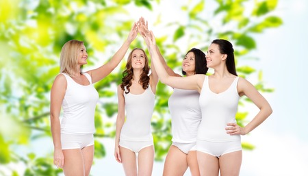 mid age: gesture, friendship, beauty, body positive and people concept - group of happy different women in white underwear making high five over green natural background