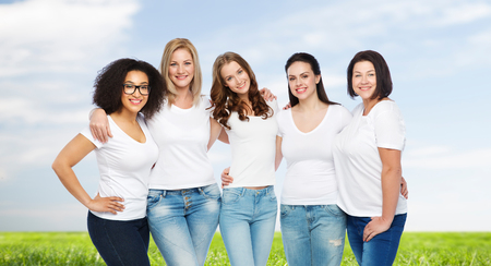 friendship, diverse, body positive and people concept - group of happy different size women in white t-shirts hugging over blue sky and grass background