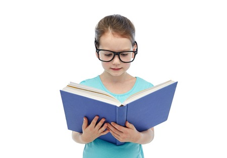 book concept: childhood, school, education, vision and people concept - happy little girl in eyeglasses reading book