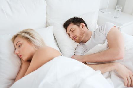 gente durmiendo: la gente, el descanso y el concepto de las relaciones - feliz pareja durmiendo en la cama en su casa