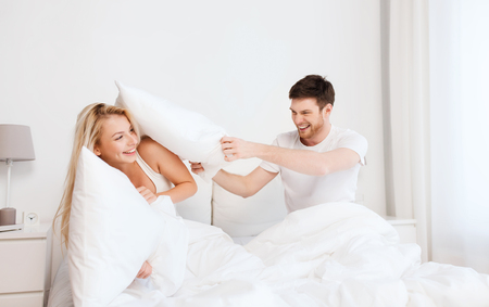 people, family, fun, bedtime and fun concept - happy couple having pillow fight in bed at home