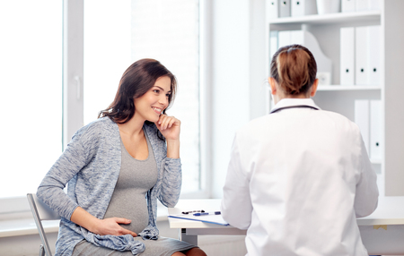 gynaecology: pregnancy, gynecology, medicine, health care and people concept - gynecologist doctor with clipboard and pregnant woman meeting at hospital Stock Photo