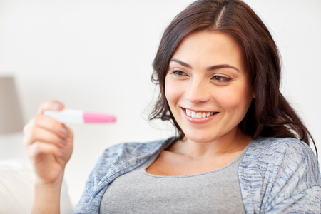 fem: pregnancy, fertility, maternity and people concept - happy smiling woman looking at pregnancy test at home
