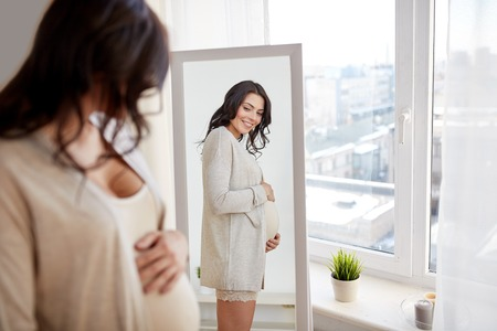 expectation: pregnancy, motherhood, people and expectation concept - happy pregnant woman looking to mirror at home Stock Photo