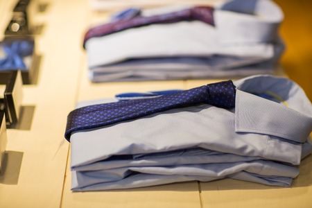 formal dressing: sale, shopping, male fashion, style and wear concept - close up of shirts with ties at clothing store