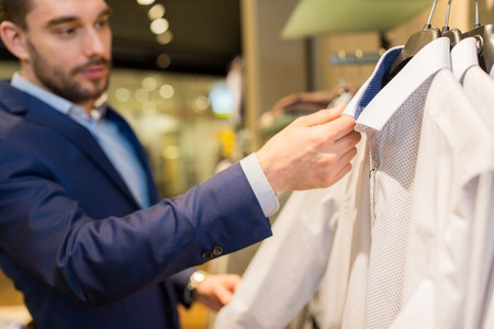 menswear: sale, shopping, fashion, style and people concept - close up of young man in suit choosing shirt in mall or clothing store