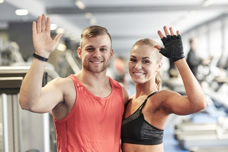welcome smile: sport, fitness, lifestyle, gesture and people concept - smiling man and woman waving hands in gym Stock Photo