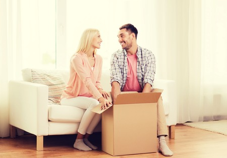 boite carton: people, delivery, shipping and postal service concept - happy couple opening cardboard box or parcel at home