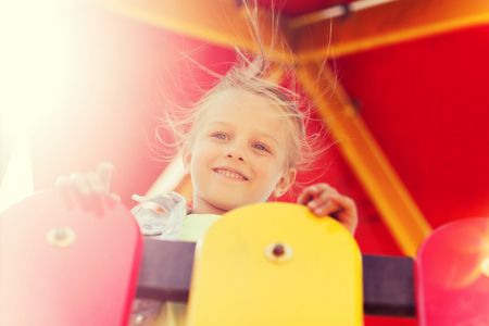 climbing frame: summer, childhood, leisure and people concept - happy little girl on playground climbing frame Stock Photo