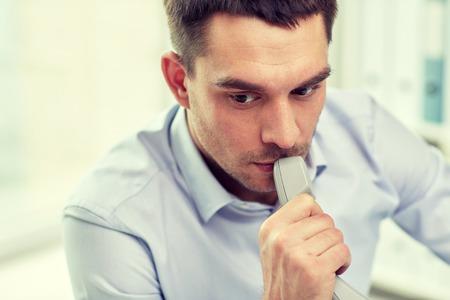 비즈니스, 사람들 및 통신 개념 - 사무실에서 전화 수신기와 사업가의 얼굴
