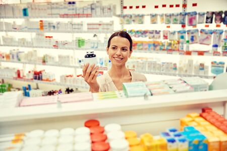 health care and medicine: medicine, pharmaceutics, health care and people concept - happy female customer with drug jar at pharmacy