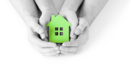 real estate and family home concept - closeup picture of male and female hands holding green blank paper house Stock Photo