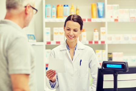 la médecine, la pharmacie, les soins de santé et les gens concept - pharmacien prescription lecture et homme senior à pharmacie caisse enregistreuse Banque d'images
