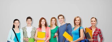 students group: education, school and people concept - group of smiling teenage students with folders and school bags over gray background Stock Photo