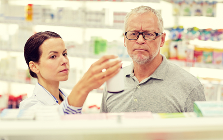 druggist: medicine, pharmaceutics, health care and people concept - pharmacist showing drug to senior man customer at drugstore