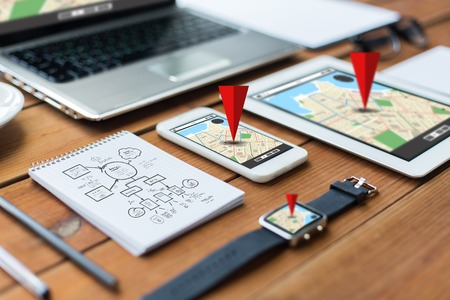 travel location: navigation, travel and technology concept - close up of laptop computer, tablet pc, notebook and smartphone with scheme and gps navigator map on wooden table