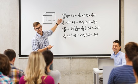 education, high school, mathematics and people concept - student standing with remote control in front of teacher and classmates and showing mathematical equalities on white board in classroom