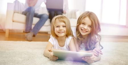 las personas, la familia, la tecnología y los niños concepto - felices niñas que juegan con la computadora Tablet PC en el hogar