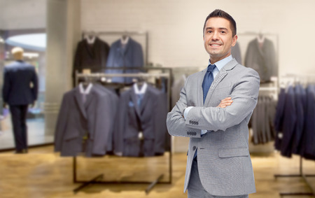 menswear: business, people, menswear, sale and clothes concept - happy smiling businessman in suit over clothing store background