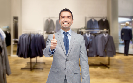 formal dressing: business, people, menswear, sale and clothes concept - happy smiling businessman in suit over clothing store background showing thumbs up