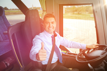 intercity: transport, tourism, road trip and people concept - happy driver driving intercity bus and snowing thumbs up