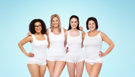 hispanic woman: friendship, beauty, body positive and people concept - group of happy women different in white underwear over blue background Stock Photo