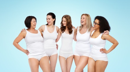 women in underwear: friendship, beauty, body positive and people concept - group of happy women different in white underwear over blue background Stock Photo