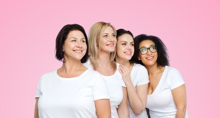 women friendship: friendship, diverse, body positive and people concept - group of happy different size women in white t-shirts over pink background