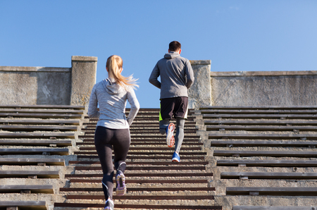 sport fitness: fitness, sport, exercising and lifestyle concept - couple running upstairs on stadium Stock Photo