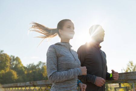 personas trotando: fitness, sport, people and jogging concept - happy couple running outdoors