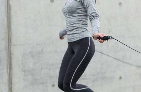 fitness, sport, les gens, l'exercice et le concept de mode de vie - close up de la femme sauter avec une corde à sauter en plein air