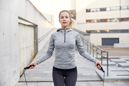 sport woman: fitness, sport, people, exercising and lifestyle concept - woman skipping with jump rope outdoors