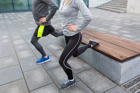 lunge: fitness, sport, people, exercising and lifestyle concept - close up of couple couple doing lunge exercise on city street