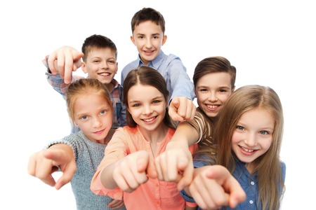 childhood, fashion, friendship and people concept - happy smiling children pointing finger to you Banco de Imagens