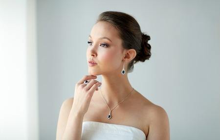 diamond necklace: beauty, jewelry, people and luxury concept - beautiful asian woman or bride with earring, finger ring and pendant