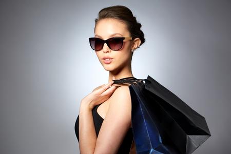 판매, 패션, 사람과 럭셔리 컨셉 - 회색 배경 위에 쇼핑 가방과 함께 검은 선글라스에 아름 다운 젊은 여자를 행복