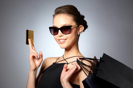 venda, finanças, moda, pessoas e conceito de luxo - mulher nova feliz bonita em óculos de sol pretos com sacos de cartão de crédito e de compra sobre o fundo cinzento