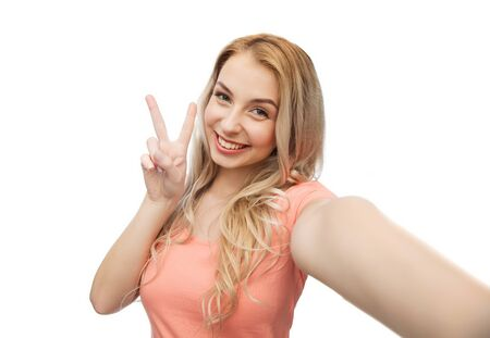 emotions, expressions and people concept - happy smiling young woman taking selfie and showing peace hand sign