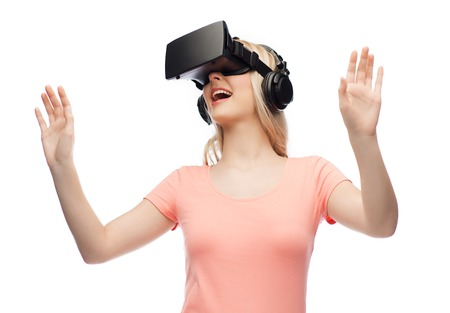 mediated: technology, virtual reality, entertainment and people concept - happy young woman with virtual reality headset or 3d glasses and headphones playing game Stock Photo