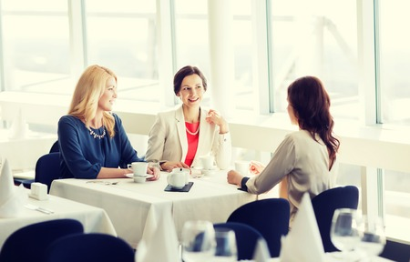 middle age: people, communication and lifestyle concept - happy women drinking coffee and talking at restaurant Stock Photo
